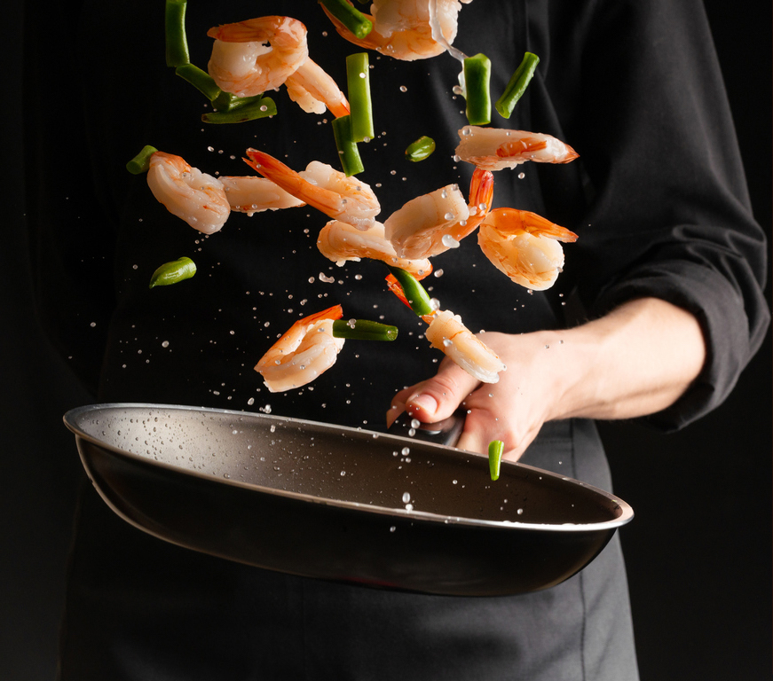 A Chef tossing peeled prawns and green beans on top of a wok