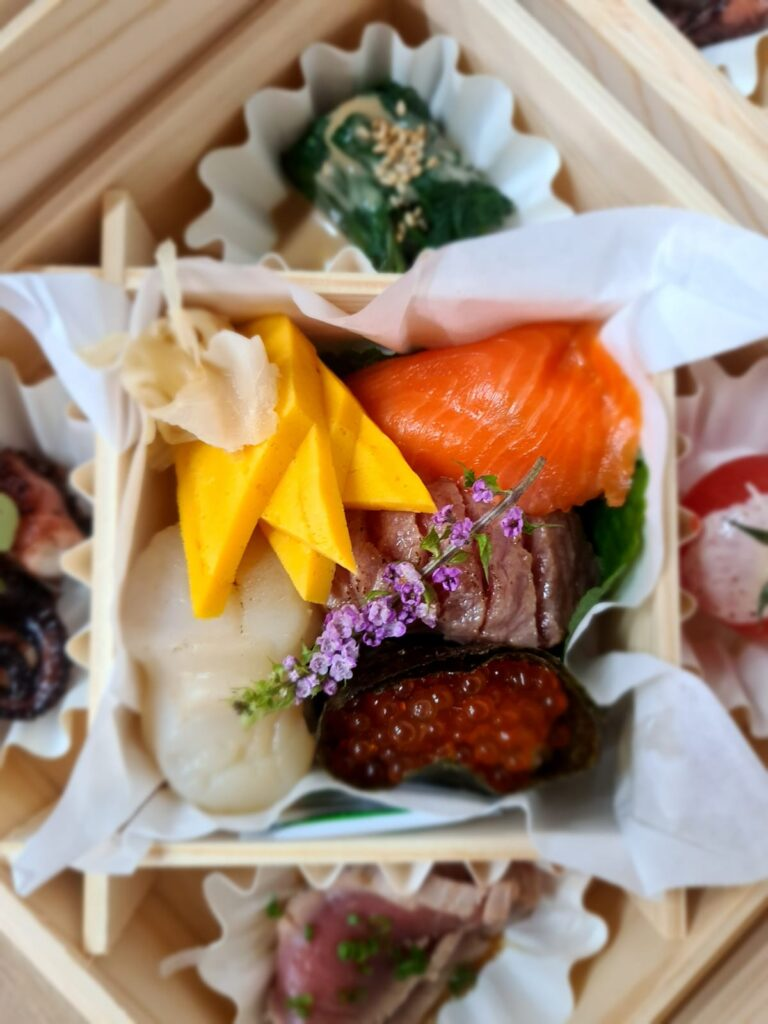 Close up on essplore's omakase otoro dish showcasing scallop, ikura nigiri, salmon and more